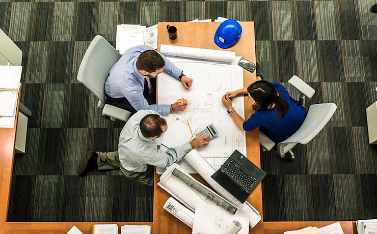 Picture of architects at work studying plans. The workflow in architecture firms can be improved significantly by the use of project management software specifically for architecture.
